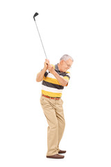 Profile shot of a senior swinging a golf club