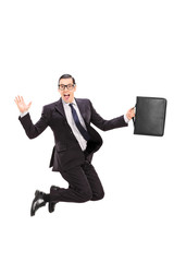 Businessman holding a case and jumping in the air