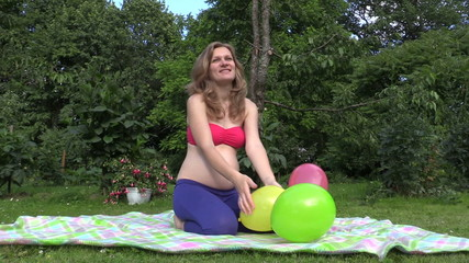 pregnant smiling woman play with colorful balloon in green park