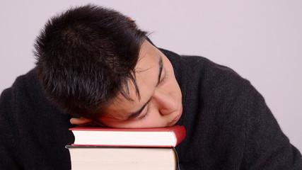 mann schläft auf büchern