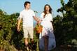 Couple walking in between rows of vines