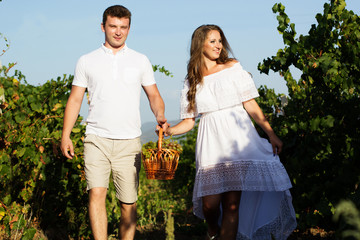 Couple walking in between rows of vines