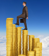 Businessman climbing stairs of gold coins