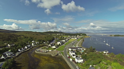 Camera flying over small port with sailing boats in town of Kyle