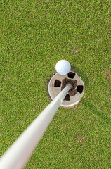 Aerial view of golf ball near pin and hole on green grass of gol