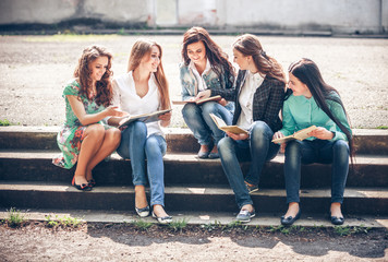 Group of students sitting with a books on street
