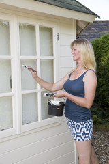Woman in mini skirt painting exterior of garden office