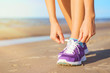 Woman wearing running shoes on the beach - 70031631