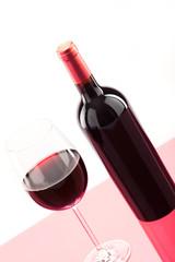 Ein Glas Rotwein mit Flasche daneben