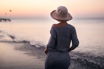 Молодая девушка у берега моря на закате