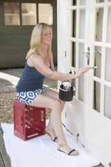 Attractive painter in mini skirt painting garden office