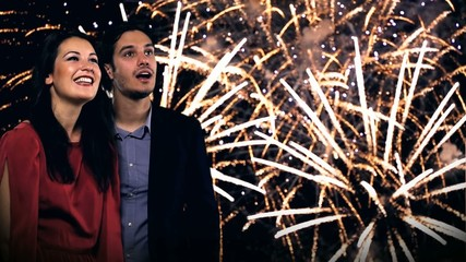 young couple looking at new year's fireworks
