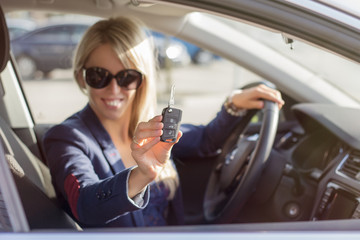 Happy young woman showing her new car keys
