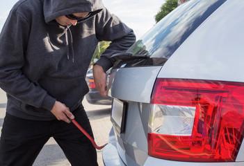 Thief breaking door lock of a car