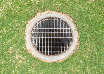 Floor drain contrast with green grass background in the garden
