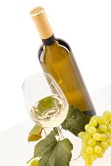 Weisswein im Glas mit Trauben vor weissem Hintergrund