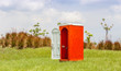 Standalone of red water closet or toilet in the green meadow wit - 70033469