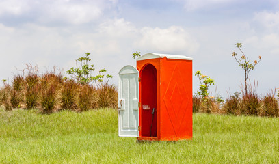 Standalone of red water closet or toilet in the green meadow wit