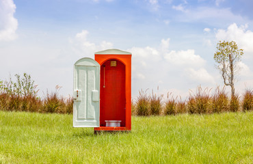 The red toilet with white door open contrast with green grass an