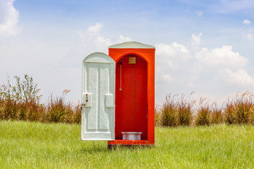 Standalone of red toilet with white door open contrast with gree
