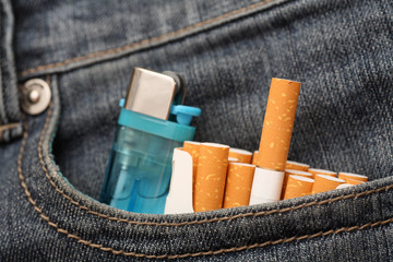 Cigarettes and lighter in pocket of jeans