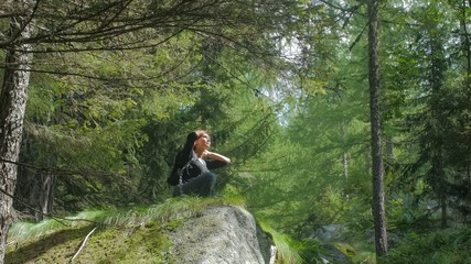 woman meditating in a wild forest