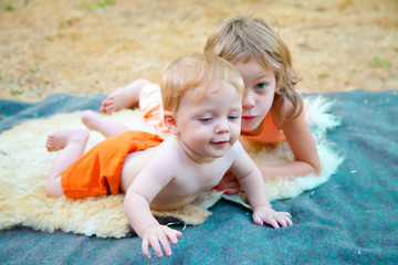 Baby boy outdoors with his sister