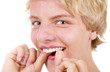 Teenager benutzt Zahnseide