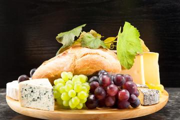 Käseplatte mit roten und grünen Weintrauben