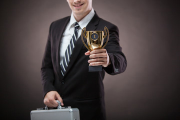 business man holding a trophy aloft