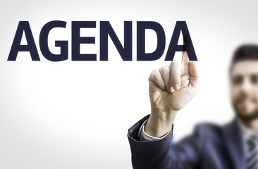 Business man pointing to transparent board with text: Agenda