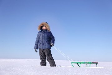 boy with sled on sky background