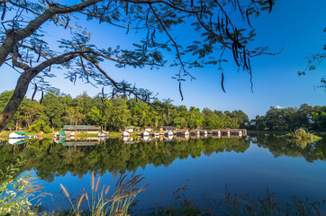 Mixed forest and bungalow reflected in the lake and blue sky
