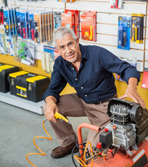Confident Senior Man With Air Compressor In Store