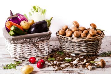 Funghi e ortaggi in cestini su tavolo di legno