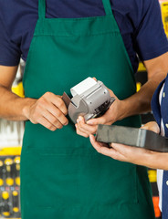 Worker Swiping Credit Card With Woman Holding Tool Set