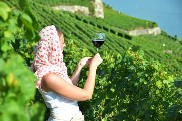 Girl tasting red wine in Lavaux, Switzerland