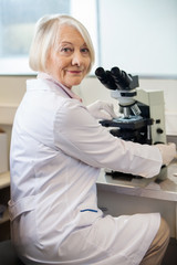Confident Female Scientist Using Microscope In Lab