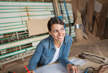 Thoughtful Female Carpenter Working On Blueprint