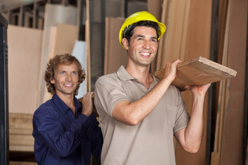 Carpenters Carrying Plank While Looking Away
