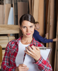 Confident Female Supervisor Holding Clipboard