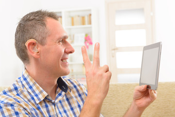 Deaf man using sign language on the tablet