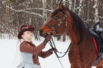woman keeps the Arab racer in  brown riding habit