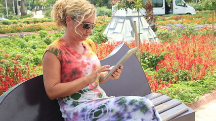 Woman sitting on the park bench and using digital tablet