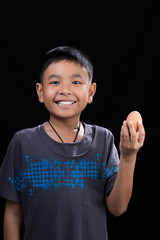 Asian kid holding egg in his hand on black background