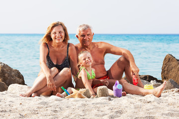 Little girl with grandparents on the beach