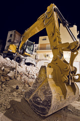 backhoe caterpillar tractor at night on house ruins