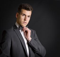 Hombre en traje de etiqueta ajusta su pajarita