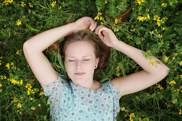 young woman sleeping in a flower meadow