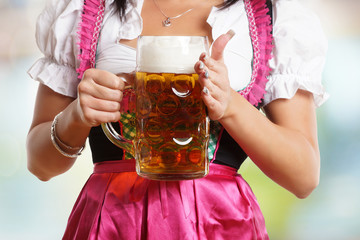 Mädchen im Dirndl hält Mass Bier